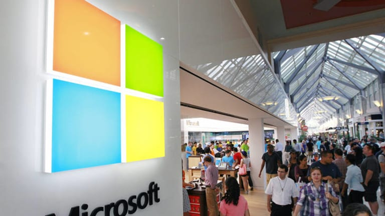 A new Microsoft logo, left, is seen on an exterior wall of a new Microsoft store inside the Prudential Center mall, in Boston.