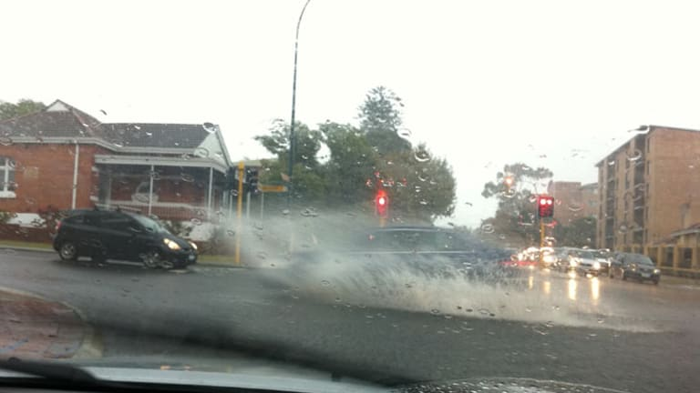 Cars negotiate large pools of water on the road in Leederville this morning.