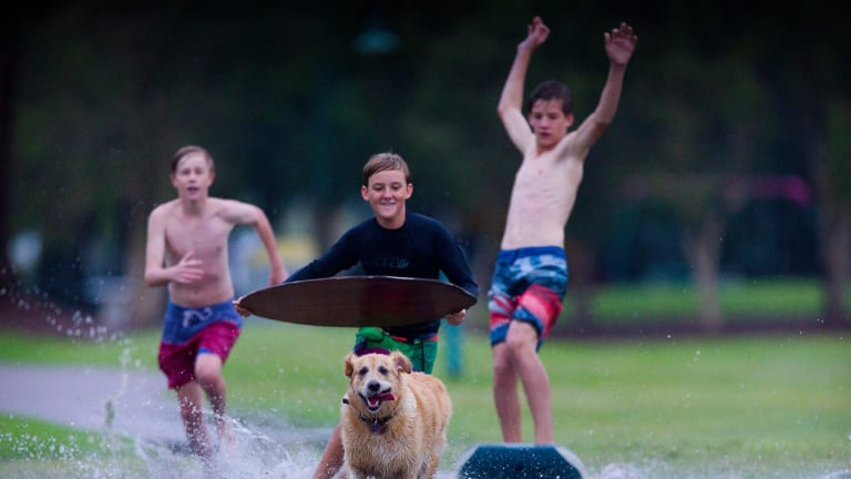 Boys jump on boogie boards in a park on the Wynnum foreshore from rain after Tropical Cyclone Marcia.