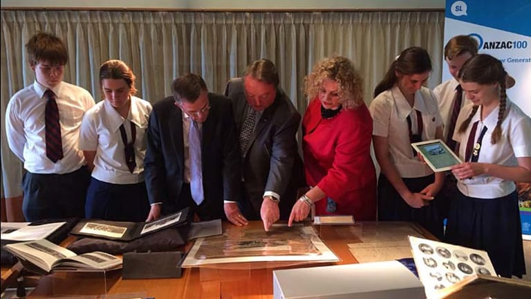 Arts Minister Ian Walker, Minister Assisting the Premier on the Commemoration of the Anzac Centenary Glen Elmes and librarian Janette Wright inspect WWI treasures with Brisbane State High School students.