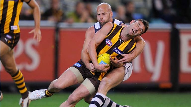 Hawthorn's Brent Guerra tackled by Geelong's Paul Chapman.