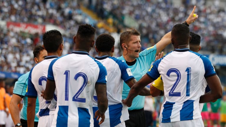 Referee Daniele Orsato warns off Honduran players as they plead for him to reverse a penalty call in their World Cup qualifier against Australia at the Olympic Stadium in San Pedro Sula.