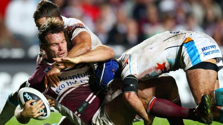 Going down ... Manly's Josh Perry is driven into the Brookvale Oval turf by the Gold Coast defence.