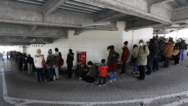 People line up to buy food at a supermarket that had been temporarily closed after the  earthquake and tsunami hit Sendai.