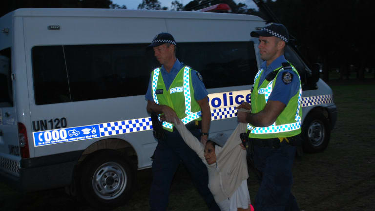 Police drag away and arrest protester Peta Garlett during the morning raid