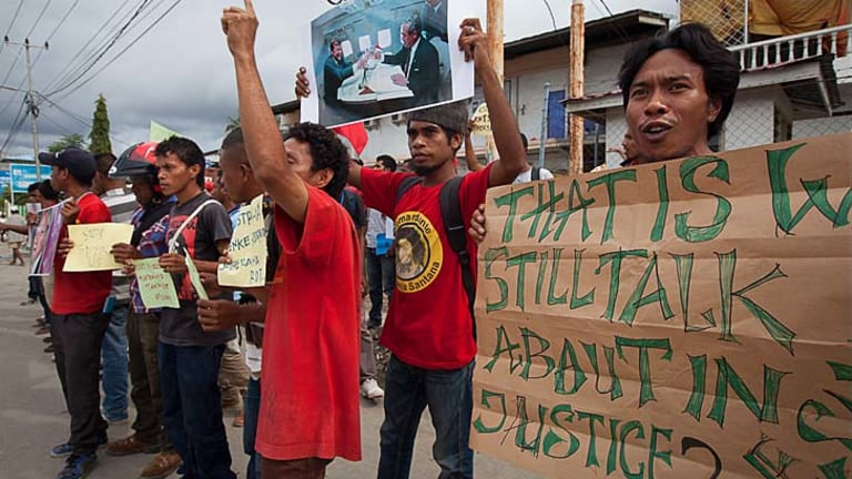 Spying scandal: Protesters hold up signs during an anti-Australia rally in Dili, East Timor. The protests were in response to allegations government offices were bugged by Australian authorities.