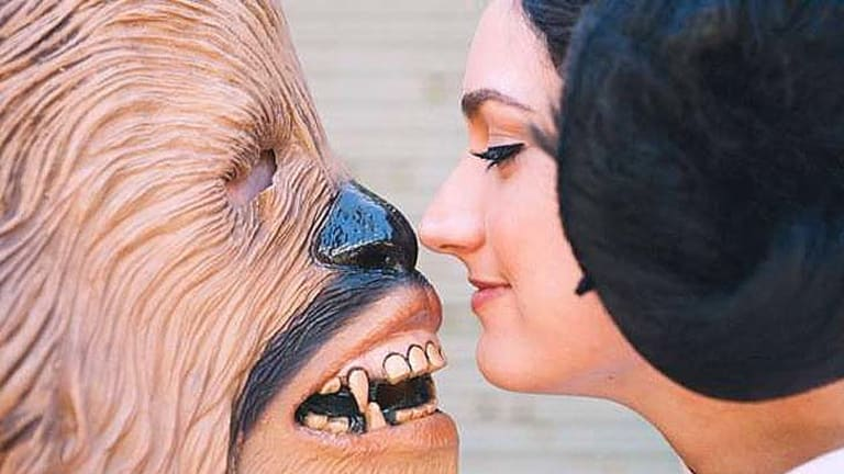 """""""Chewbacca"""" and """"Princess Leia"""" seal their marriage with a kiss during a Star Wars themed wedding."""