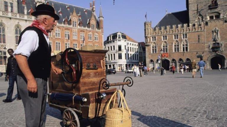 Pipeline to reduce Traffic on Bruges cobblestoned alleys: A man plays a barrel organ in Bruges' market square.