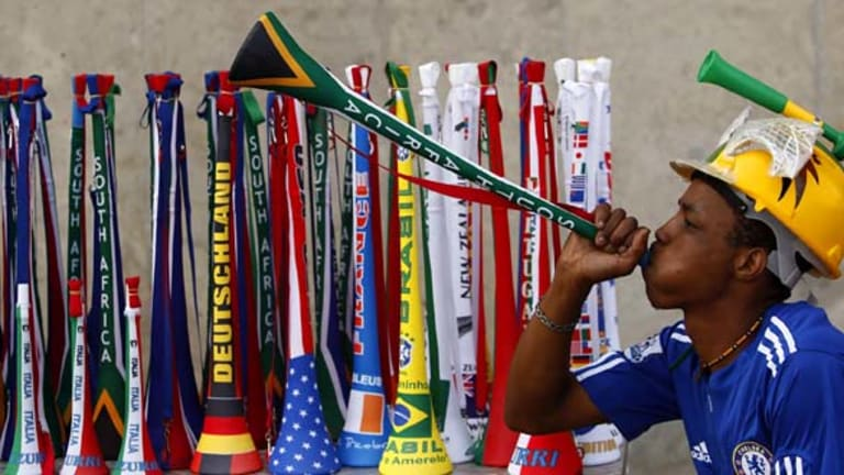 A street vendor blows a vuvuzela as he tries to attract customers.