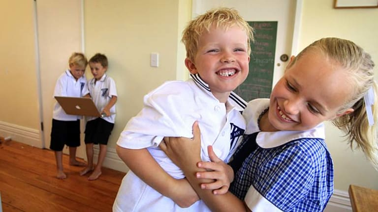 Age of technology: Bella Walker, 7, Rupert Perry, 5, with James Walker, 5, and Max Perry, 6, in the background with a laptop.