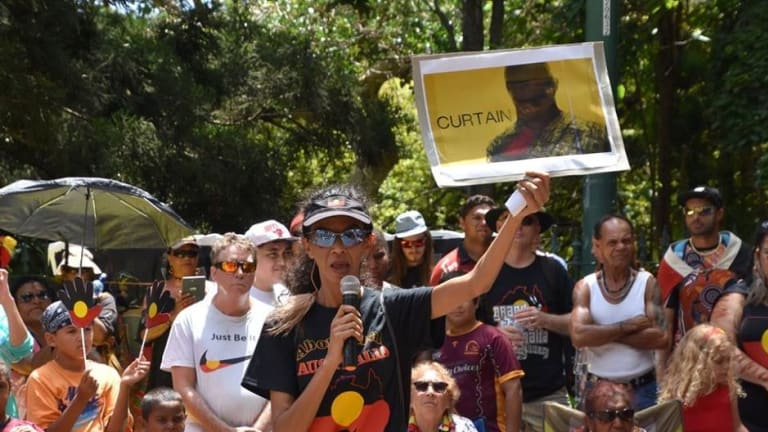 Gwenda Stanley holds up an image in support of Kevin Henry at a recent Invasion Day rally.