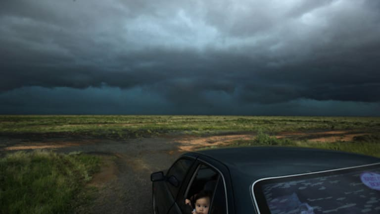 Should I wind up the window, Mum? … Jimelle Deguara watches a hailstorm break over the Hay region.