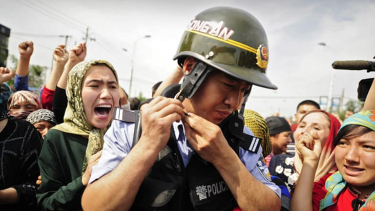 Mass unrest … Uighur women surround a Chinese riot policeman during protests in Urumchi, the capital of Xinjiang province, last July.