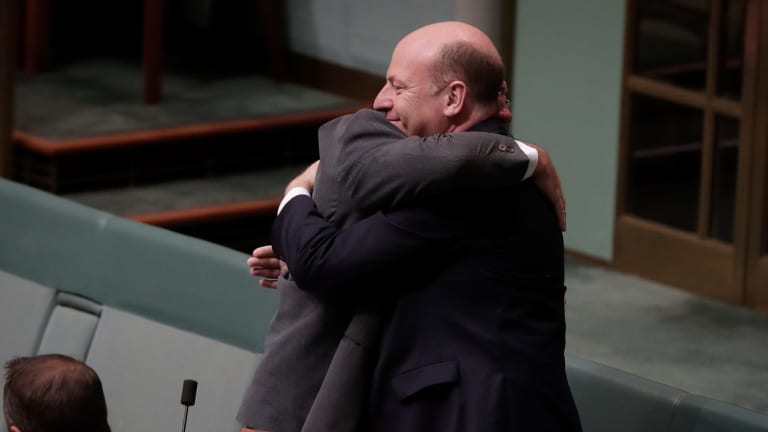 Warren Entsch embraces Liberal MP Trent Zimmerman after he spoke during debate on the Marriage Amendment Bill in the House of Representatives at Parliament House in Canberra on Monday 4 December 2017. fedpol Photo: Alex Ellinghausen