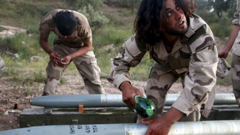Tajammu Al-Ezza brigade fighters prepare shells to fire at the Assad forces on Friday.