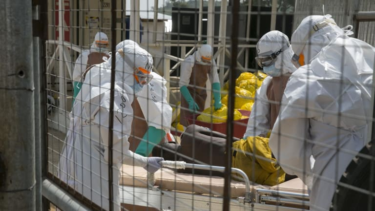 Health workers lift a newly admitted patient onto a wheeled stretcher in an Ebola treatment centre in Freetown in December.