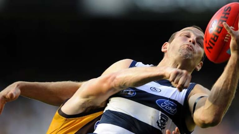 Geelong's best player yesterday, Brad Ottens, gets the better of his Hawthorn opponent in this battle for the ball at the MCG.
