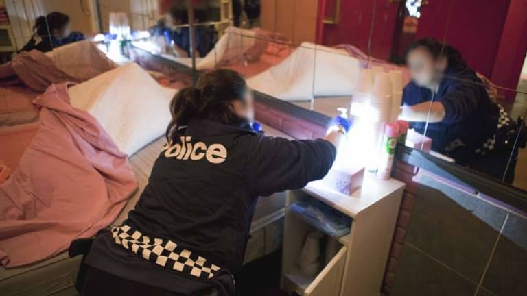 A police officer searches one of the four brothels raided on Tuesday.