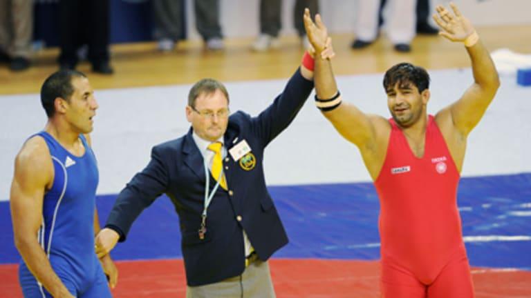 The decision ... India's Anil Kumar is awarded the gold medal, as Australia's Hassene Fkiri looks on.