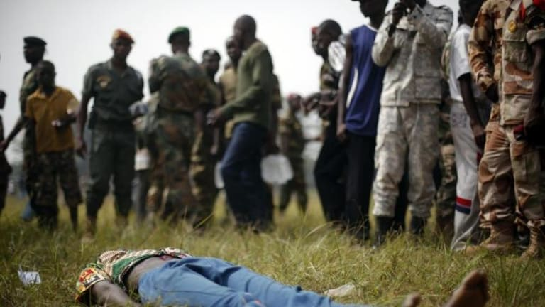 A man lies wounded after being stabbed by newly enlisted soldiers moments after Central African Republic Interim President Catherine Samba-Panza addressed the troops in Bangui.