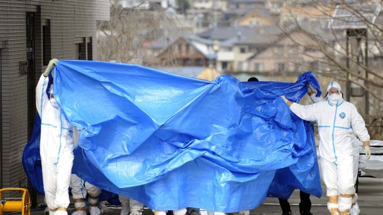Workers who stepped into radiation-contaminated water at the Fukushima Dai-ichi nuclear plant are shielded with tarps before receiving decontamination treatment.
