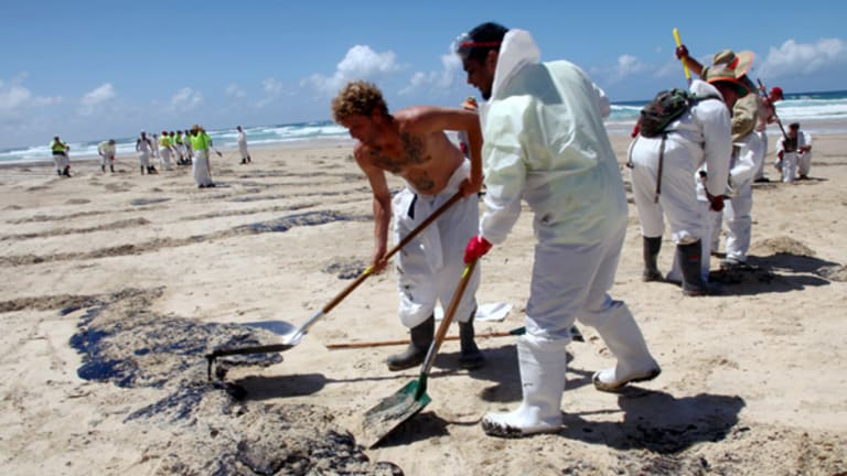 Workers clean up the oil that has spilled on to the coast of Moreton Island.