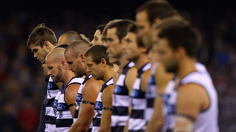 Reverential: Geelong players bow their heads in tribute to legendary Cat player and coach Bob Davis.