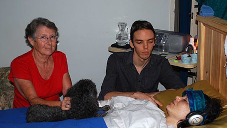 Theda Myint's mother Carol Adams and her partner Blake Graham, along with the family dog Maggie, keep a vigil at her bedside at their Willetton house.