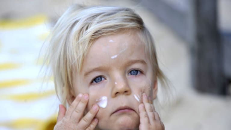 Care factor... Noah Ellison-Baker, 2, at Clovelly Beach yesterday, rubbing in sunscreen applied by his mum Katie.