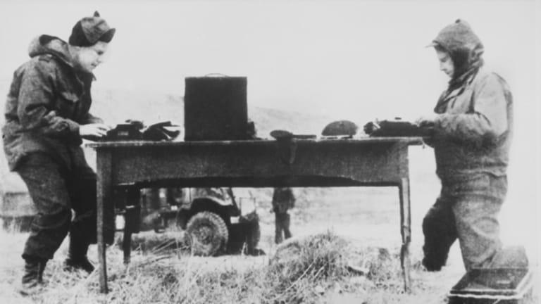 Harry Gordon (right), writing a story in Korea 1951.
