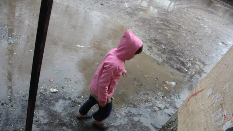 A child plays in the sodden Serres refugee camp in northern Greece.