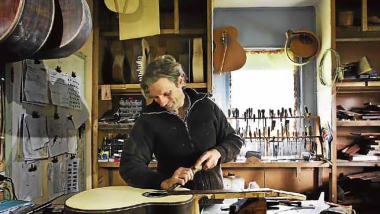 Jack Spira works on a guitar.