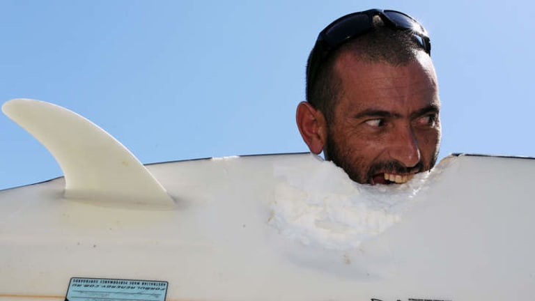 Close shave … Glen Folkard with his shark-bitten surfboard.