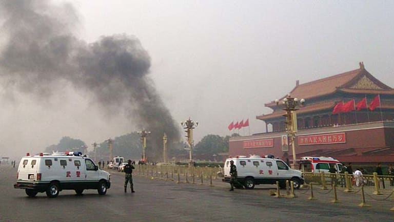 Police cars block off the roads leading into Tiananmen Square as smoke rises into the air after a vehicle crashed in front of Tiananmen Gate on Monday.