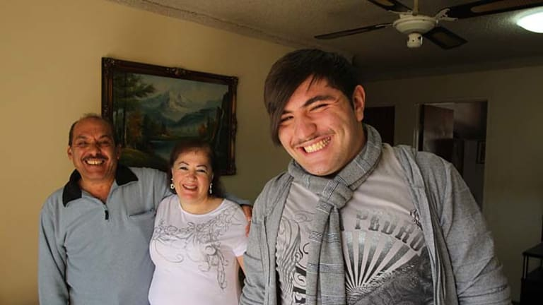 Proud... university student Raed El-Essraoui with his parents, Ghassan and Wafaa, has bucked the trend.