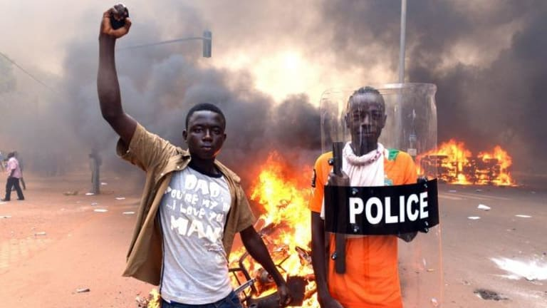 Protesters with a police shield outside parliament in Ouagadougou.