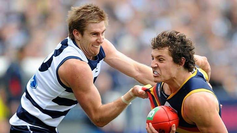Geelong's Tom Lonergan tackles Adelaide's Kurt Tippett at Skilled Stadium.