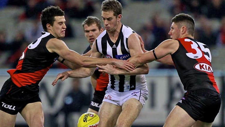 Two on one: Collingwood captain Nick Maxwell is put under pressure by young Bombers Jackson Merrett and Nick O'Brien at the MCG last night.