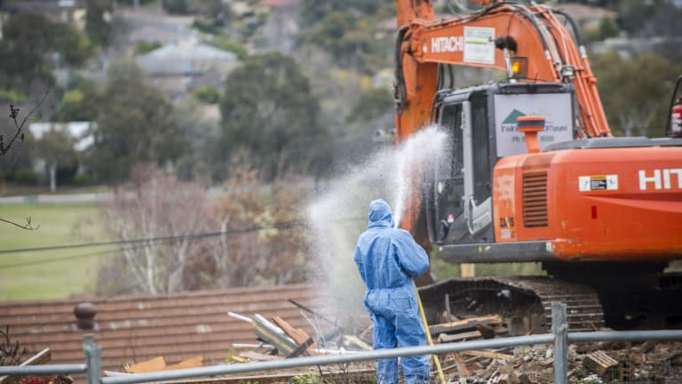 Workers demolish a Mr Fluffy home in Farrer. The government's offer to buy homes at market value ends on June 30.