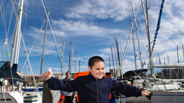 Member of the group Sailors with DisABILITIES Khan Cawaitakali plays among boats as the group prepares to sail to northern NSW.