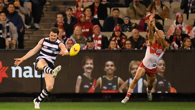 Swan dive: Sydney's Jarrad McVeigh, in his 300th game, tries to spoil Patrick Dangerfield of the Cats.