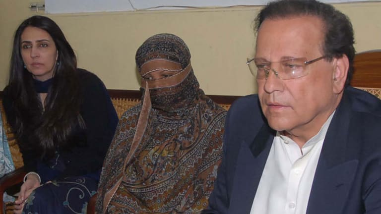 Asia Bibi, centre, listens to the then Pakistani Punjab province governor, the late Salman Taseer.