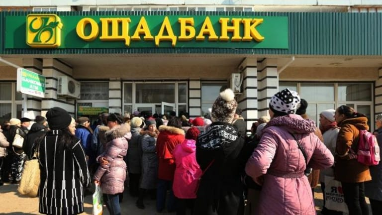 Large crowds gather at the entrance of the Oschadbank in the town of Djankoy.