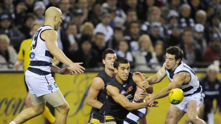 Carlton's Andrew Carrazzo forces out a handball while Cat Gary Ablett awaits the outcome of the contest at Etihad Stadium on Friday night.