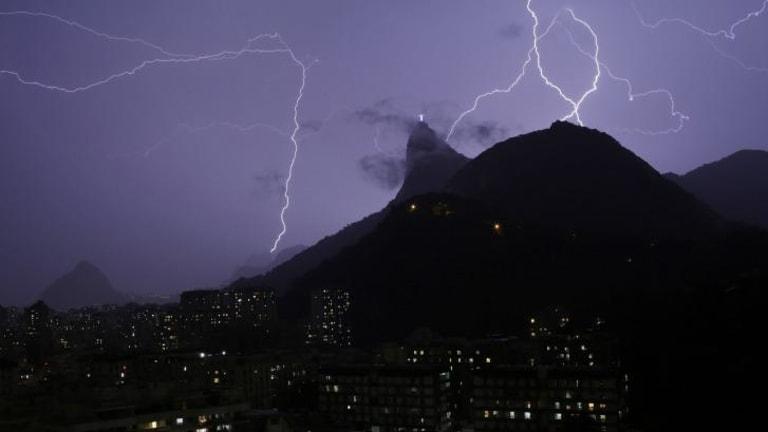 Lightning bolts strike through the sky near Christ the Redeemer.
