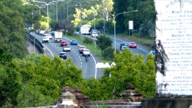 Traffic passes by the Toowong Cemetery.
