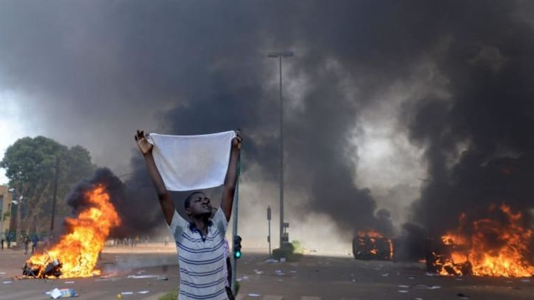 Protester holds a white cloth up as cars and documents burn.