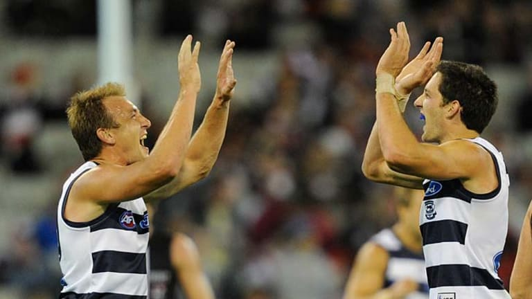 Geelong's Darren Milburn celebrates the Cats win against St Kilda in round one with Harry Taylor.