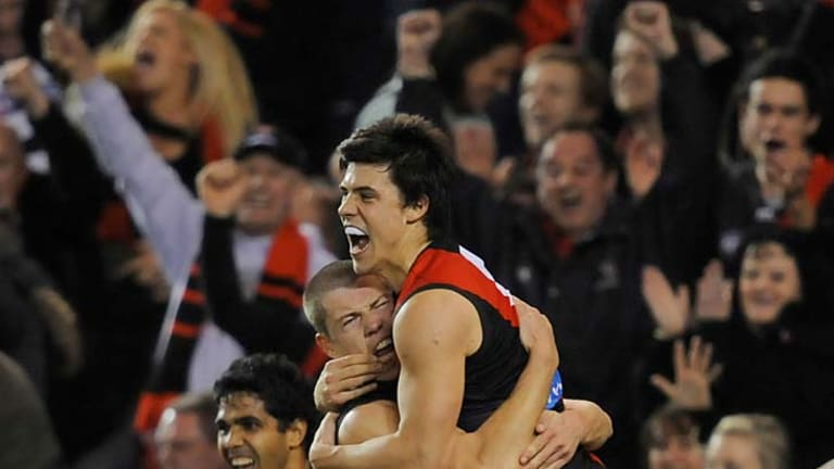 Essendon's Angus Monfries and Jake Melksham celebrate a final goal last night in their surprise win over the Cats.