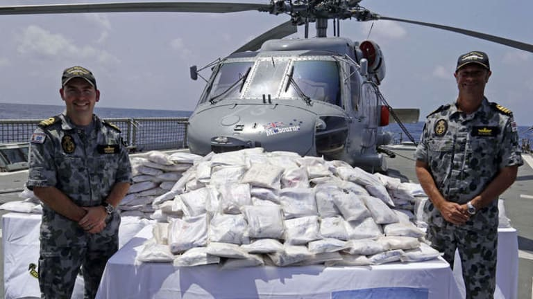 Crew members of HMAS Melbourne with seized drugs prior to them being destroyed.